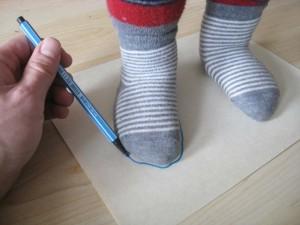 Die Kinderfüße stehen auf einem Blatt Papier und werden mit einem Filzstift umzeichnet