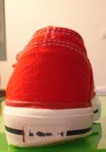 Roter Chucks-mäßiger Kinderturnschuh mit stark auf einer Seite abgelaufener Sohle